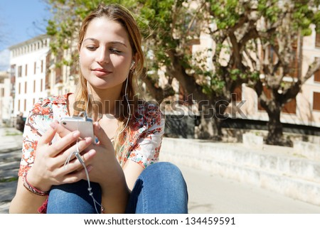 Portrait of an attractive hispanic young woman listening to music with her smartphone in the city during a sunny day. - stock photo