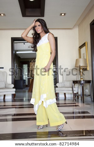 portrait of an attractive Indian female model wearing traditional Indian yellow dress