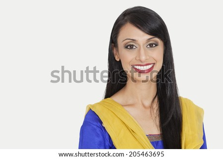 Portrait of an attractive Indian woman in traditional wear smiling against gray background - stock photo