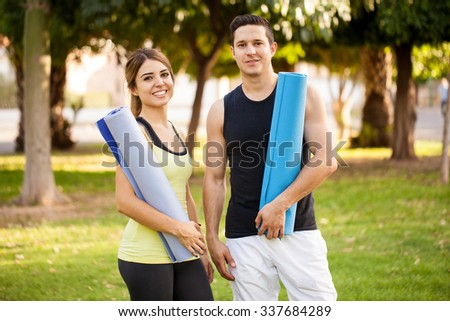 Portrait of an attractive Latin couple holding exercise mats and ready for their yoga practice