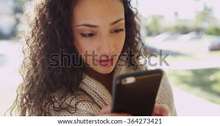 Portrait of an attractive latino woman texting on a cell phone.