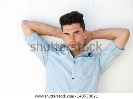 Portrait of an attractive male fashion model with hands behind head