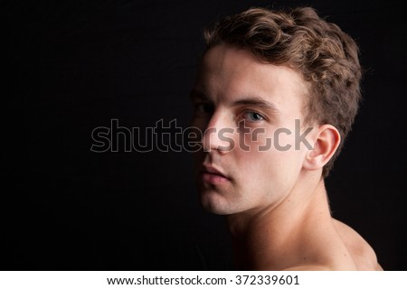 Portrait of an attractive man in front of a black background - stock photo