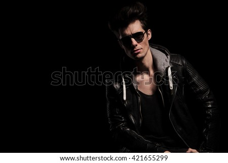 portrait of an attractive man in leather jacket posing in studio - stock photo