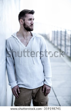 Portrait of an attractive man leaning on a wall - stock photo