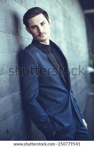 Portrait of an attractive man, model of fashion, wearing modern suit. - stock photo
