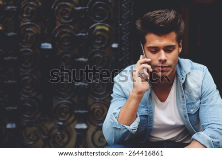 Portrait of an attractive man talking on his smart phone sitting outdoors, handsome young man speaking on cellphone with copy space, fashionable man using his mobile phone in urban setting - stock photo