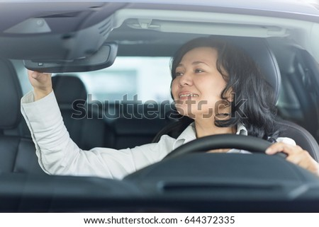 Portrait of an attractive mature Asian woman smiling adjusting rearview mirror sitting in a car driving safety comfortable luxury living lifestyle travelling automobile vehicle technology transport