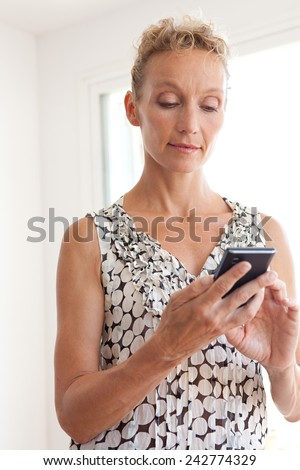 Portrait of an attractive mature professional business woman standing in an office space and using a smartphone device to connect on line, workplace interior. Senior businesswoman using technology. - stock photo