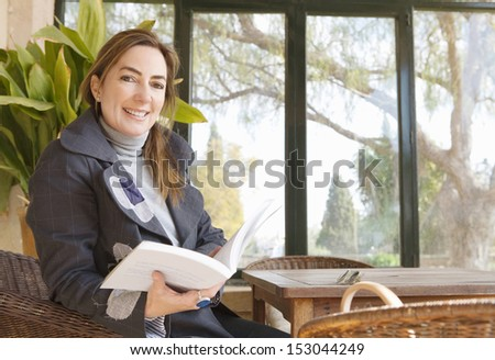 Portrait of an attractive mature woman sitting at a home conservatory garden table at home, smiling at the camera during a winter day and relaxing holding an open book. - stock photo