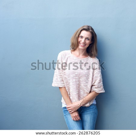 Portrait of an attractive mid adult woman smiling on gray background - stock photo