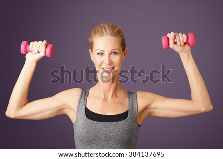 Portrait of an attractive middle age woman working out with dumbbells while standing at isolated background.  - stock photo