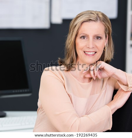 Portrait of an attractive middle-aged blond businesswoman leaning on the back of her chair in the office smiling at the camera - stock photo
