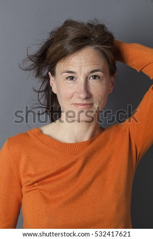 portrait of an attractive middle aged woman holding her sexy long brown hair for natural beauty and seduction, grey background studio