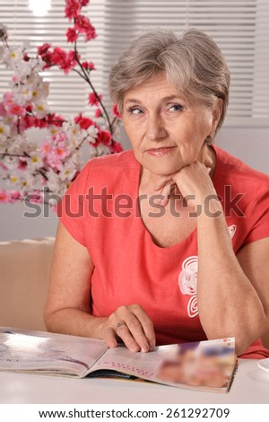 Portrait of an attractive middle-aged woman in a red dress reading magazine - stock photo