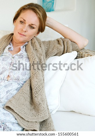 Portrait of an attractive middle aged woman laying and relaxing on a white sofa in a neutral living room at home, being thoughtful and serene, interior. - stock photo