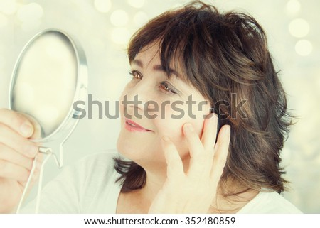 Portrait of an attractive middle aged woman looking into a mirror