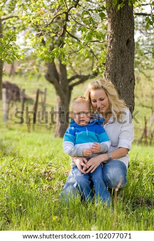 Portrait of an attractive mom and her son outdoors in the garden at spring. - stock photo