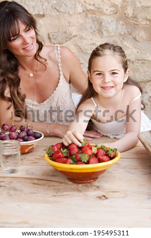 Portrait of an attractive mother and her young daughter eating fresh fruit in a holiday home outdoors, with the girl reaching to pick a strawberry from the wood table. Healthy family lifestyle living.
