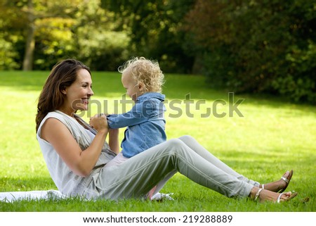 Portrait of an attractive mother playing with cute baby outdoors - stock photo