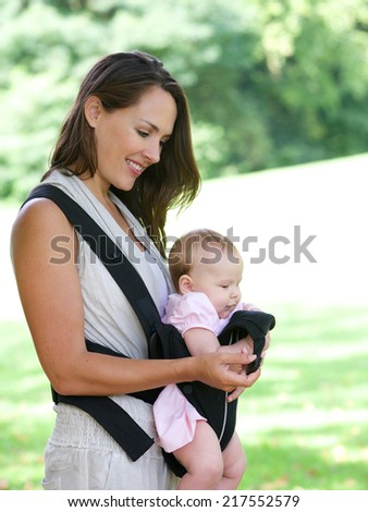 Portrait of an attractive mother smiling with baby in sling - stock photo
