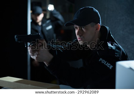 Portrait of an attractive policeman aiming gun during action