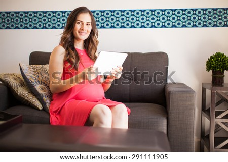 Portrait of an attractive pregnant woman relaxing in the living room and reading on a tablet computer - stock photo