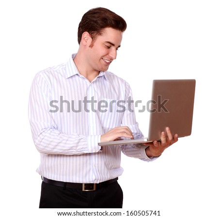Portrait of an attractive redhead man working on his laptop while smiling and standing on isolated studio