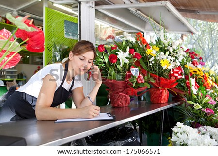Portrait of an attractive shop assistant woman and small business owner using her smartphone to take an order over the phone in her florist kiosk market stall store. Outdoors business.