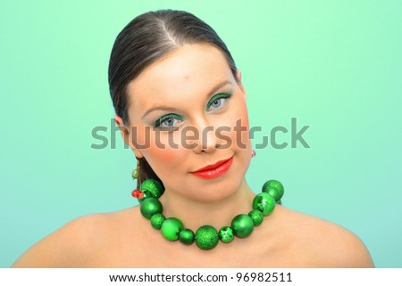 Portrait of an attractive slav woman in green decoration - stock photo