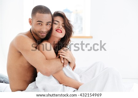 Portrait of an attractive smiling sensual young couple caressing laying in bed together - stock photo