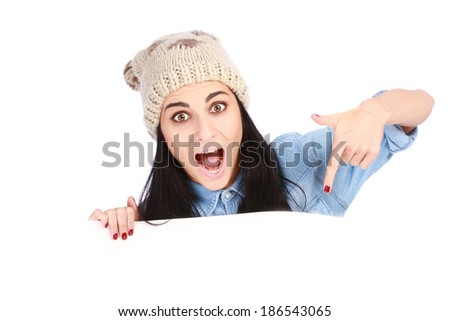 Portrait of an attractive smiling teenage pointing her finger at white billboard against white background