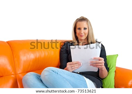 Portrait of an attractive smiling thoughtful young woman reading a paper - stock photo