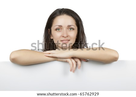 Portrait of an attractive smiling woman leaning on blank board against white background