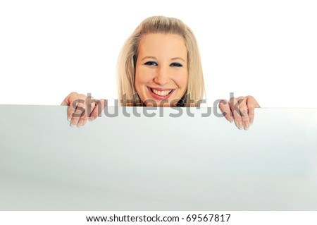 Portrait of an attractive smiling young woman peeping or looking over a white board against white background - stock photo
