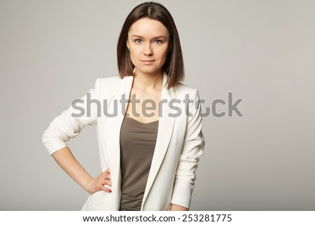 Portrait of an attractive stylish young brunette woman. On Grey - stock photo