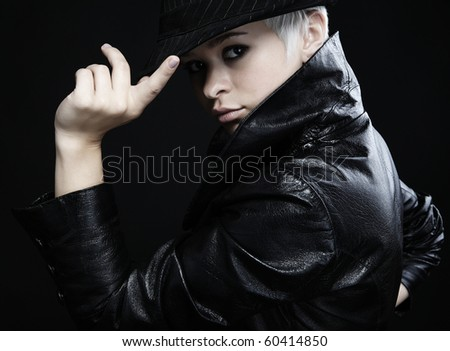 Portrait of an attractive teenage girl posing against white background on leather jacket&hat - stock photo