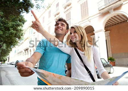 Portrait of an attractive tourist young couple relaxing sightseeing and visiting a destination city on holiday, pointing up and enjoying traveling together, outdoors. Tourism, travel and lifestyle.