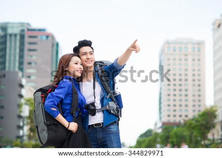 Portrait of an attractive tourist young couple relaxing sightseeing and visiting a destination city on holiday, pointing up and enjoying traveling together, outdoors. Tourism, travel and lifestyle. - stock photo