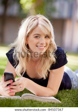 Portrait of an attractive university student sending a text message on a cell phone - stock photo