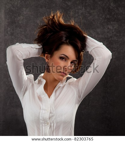 portrait of an attractive woman in a white blouse on a black background - stock photo