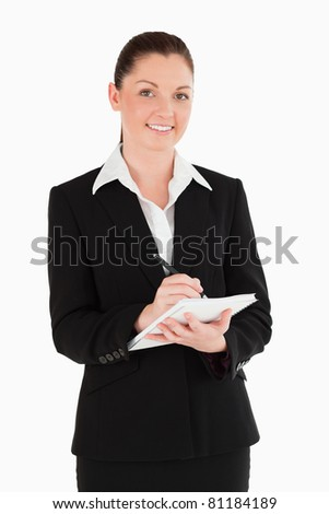 Portrait of an attractive woman in suit writing on a notebook while standing against a white background - stock photo