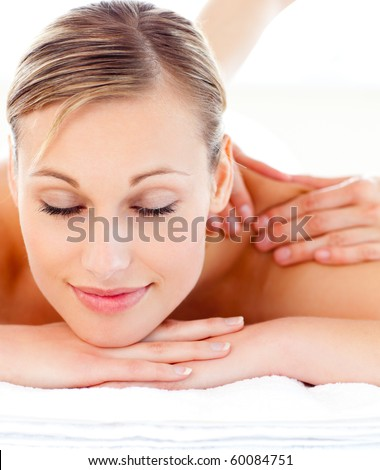 Portrait of an attractive woman lying on a massage table in a health spa - stock photo