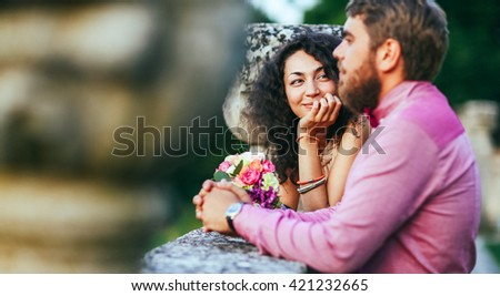 Portrait of an attractive woman seriously listening to her boyfriend while on a date. Man with beard, woman with curly hair. - stock photo