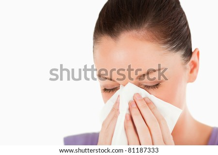 Portrait of an attractive woman sneezing while standing against a white background - stock photo