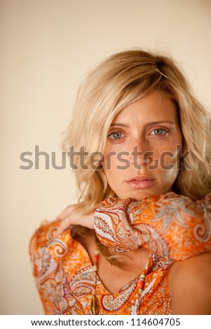 Portrait of an attractive woman wearing a tropical orange shirt. - stock photo