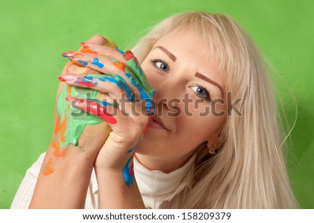 Portrait of an attractive woman with hands in fresh paint - stock photo