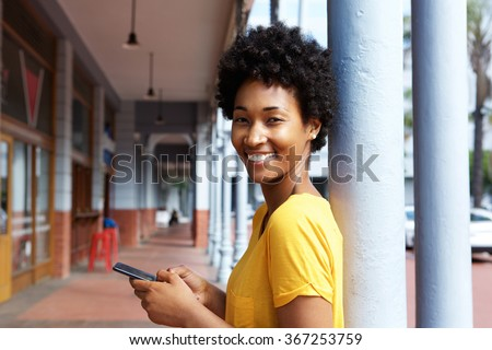 Portrait of an attractive young african woman holding a mobile phone leaning to pillar outdoors - stock photo