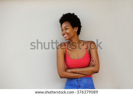 Portrait of an attractive young african woman standing with her arms crossed and looking at copy space - stock photo
