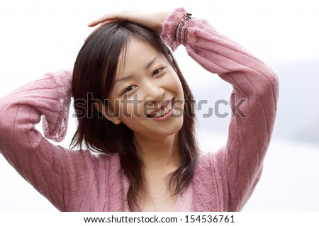 Portrait of an attractive young asian woman smiling while visiting and contemplating a beautiful lake landscape during an autumn cloudy and rainy day, outdoors. - stock photo
